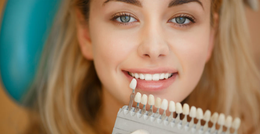 A woman smiling as she looks through veneers